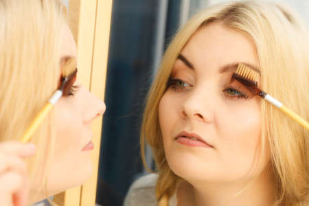 Close up of woman doing her make up, preparing lashes using brush tool brushing eyelashes.