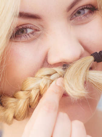 Happy funny woman having long blonde hair in two braided hairstyle. Haircare concept.
