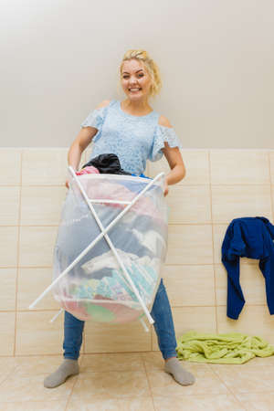 Woman in bathroom carrying big heavy basket of dirty clothes. Laundry concept. Household duties. Standard-Bild - 130066167