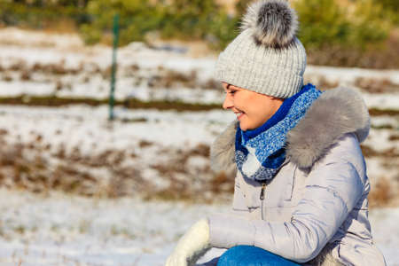 Pretty young woman wearing warm accessories during winter time. Female having grey beanie warm hat with pompons and blue scarf.