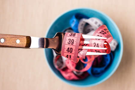 Diet food healthy lifestyle and slim body concept. Many colorful measuring tapes in blue bowl on table with fork, top view Standard-Bild