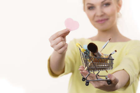 Woman holding shopping cart full of beauty accessories like various make up brushes.