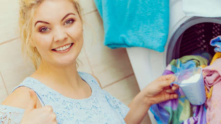 Happy woman loading dirty colorful clothes to washing machine, holding container with powder detergent. Household duties.