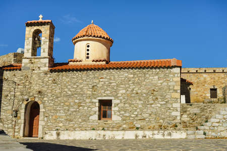 Detail of architecture stone church with traditional belfry in Vathia old town, Mani Peloponnese Greece. Architectural theme.