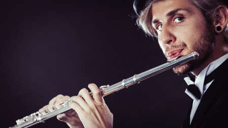 Classical music, passion and hobby concept. Elegantly dressed musician man playing on flute wearing black fedora hat. Studio shot on dark grey background