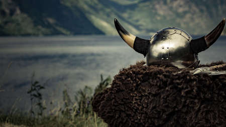 Viking helmet with axe on fjord shore in Norway. Tourism and traveling concept Stok Fotoğraf