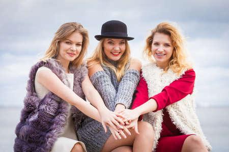 Three fashionable women having presenting pretty stylish outfits. Style, fashion, friendship concept. Imagens