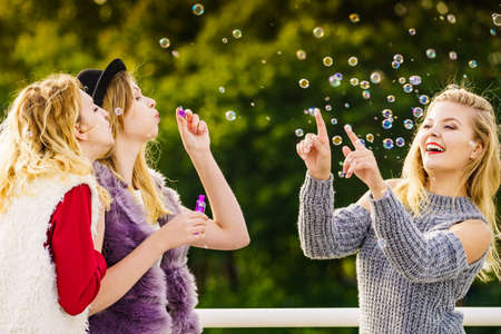 Group of young fashion women best friends having fun together blowing bubbles with toy bubble wand while enjoying sunny day outdoors. Happiness and carefree concept.