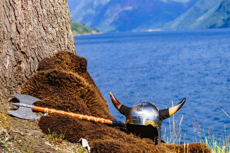 Viking helmet with axe on fjord shore in Norway. Tourism and traveling concept