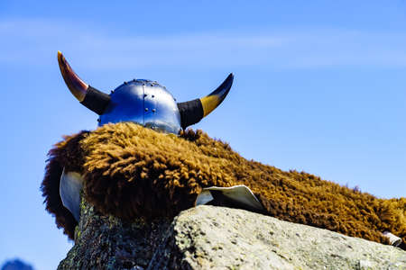 Viking helmet and brown fur against blue sky, Norway. Tourism and traveling concept