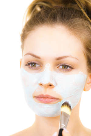 Young woman applying with brush green mud mask to face, on white. Teen girl taking care of oily skin, purifying the pores. Beauty treatment. Skincare.