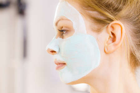 Woman with green mud mask on face, side view. Teen girl taking care of oily skin, purifying the pores. Beauty treatment. Skincare. Фото со стока