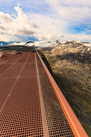 Scenic view on mountains landscape from Dalsnibba viewpoint, Geiranger Skywalk platform floor surface and glass guard rail, Norway.