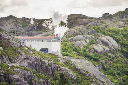 Environment pollution problem concept. Smoke from factory chimney in norwegian mountains