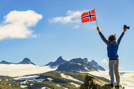 Tourist woman enjoy mountains landscape, holding norwegian flag and photo camera. National tourist scenic route 55 Sognefjellet, Norway
