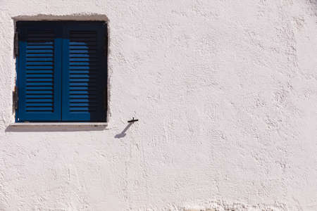 Typical Greek architecture details concept. Blue window shutters on house in Greece.