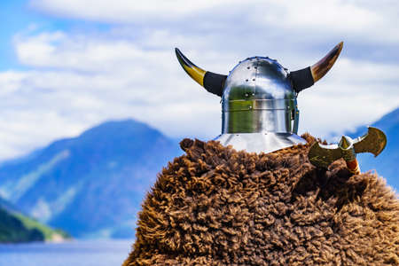 Viking warrior with helmet and axe on fjord shore in Norway. Tourism and traveling concept