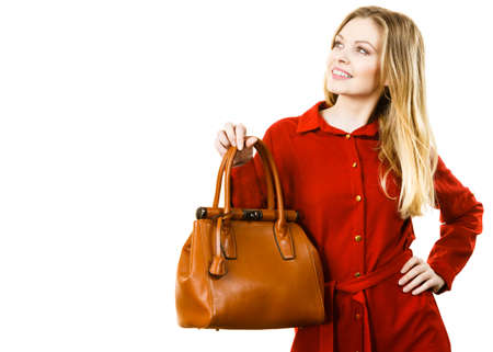 Fashionable pretty young woman wearing elegant casual red shirt and holding leather bag presenting stylish outfit.