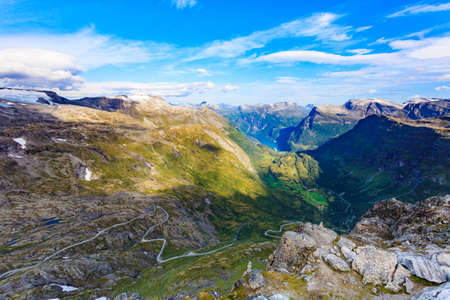 View on fjord Geirangerfjord, mountains landscape and winding road Nibbevegen from Dalsnibba viewpoint, Norway. Tourism vacation and travel.