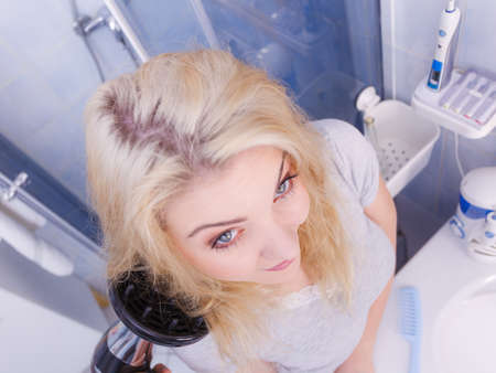 Haircare. Beauty long haired blonde woman drying hair in bathroom. Smiling girl blowing wind on wet head using hairdryer, doing curls with diffuser nozzle. Imagens