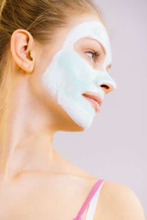 Young woman with white green mud mask on her face. Teen girl taking care of oily skin, cleaning the pores. Beauty treatment. Skincare.