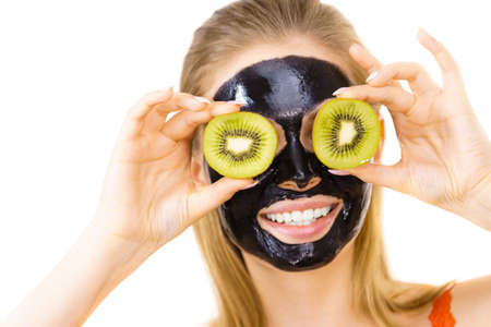 Young woman with carbo black peel-off mask on her face holding kiwi fruit halves, covering eyes, on white. Beauty treatment. Skincare.