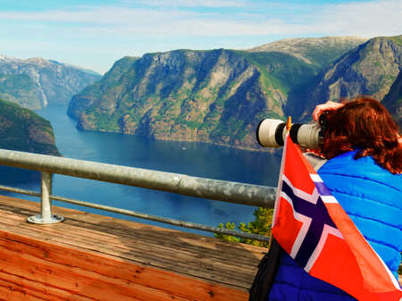 Female tourist with norwegian flag enjoying scenic view over fjord Aurlandsfjord from Stegastein viewpoint, take photos with camera. National tourist route Aurlandsfjellet. Reklamní fotografie