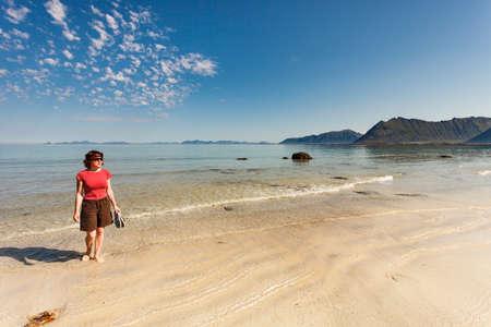 Tourist woman relaxing walking on sea shore. Coast of Gimsoya island, Gimsoysand sandy beach in summer. Nordland county, Lofoten archipelago Norway. Reklamní fotografie