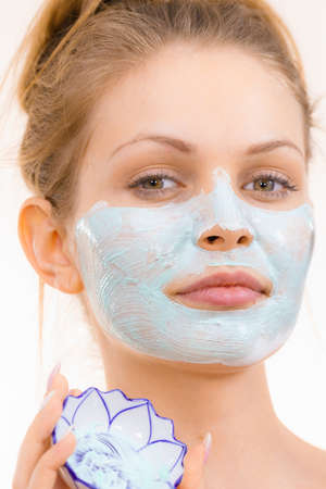 Young woman applying green mud mask to face, on white. Teen girl taking care of oily skin, purifying the pores. Beauty treatment. Skincare. Фото со стока