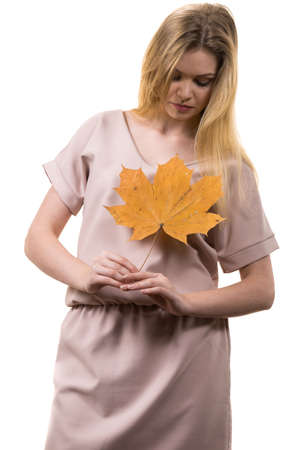 Fashionable autumn long hair blonde girl holding autumnal dry brown maple leaf in hand. Autumn, season and forecasting concept.