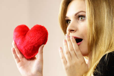 Funny woman realize falling in love. Young pretty woman having shocked face expression holding small heart shaped pillow.
