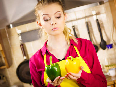 Suspicious young woman holding bell pepper vegetable thinking about meal or choosing good veggie.