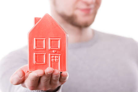 Symbolism housing safety family finances mortgage concept. Young man holding house on palm. Male presenting home model.