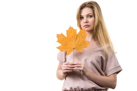 Fashionable autumn long hair blonde girl holding autumnal dry maple leaf in hand. Autumn, season and forecasting concept. Reklamní fotografie