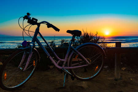 Bicycle outdoor parked on beach, evening time, sunset sky. Holidays, sport and recreation. Stok Fotoğraf