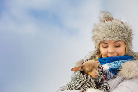 Young woman wrapped her best friend little dog in warm blanket scarf to warm him in cold winter day. Animal protection save. Adoption concept