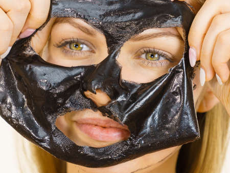 Young woman removing carbo black peel-off mask from her face. Teen girl taking care of oily skin, cleaning the pores. Beauty treatment. Skincare.