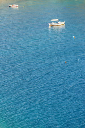 Small fishing boat, yacht on calm blue sea ocean water during warm summer weather in Greece. Stok Fotoğraf