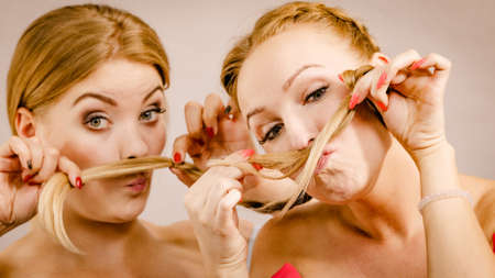 Two positive females pretending to have moustache made of hair. Friendship, leisure time together concept