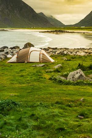 Tent on seashore in summer, cloudy hazy weather. Camping on ocean shore. Skagsanden Beach Flakstadoy Lofoten Norway. Holidays travel and adventure.