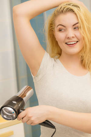 Woman drying wet armpit using hair dryer. Getting rid of sweat and bad smell, hyperhidrosis.