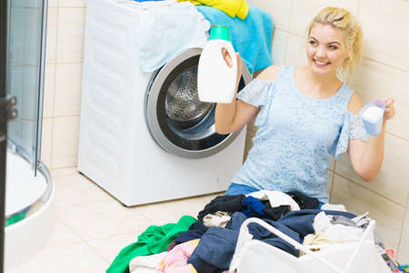 Young woman sitting in bathroom sorting clothes into washing machine. Female doing dark laundry holding liquid and powder detergent.
