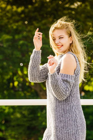 Positive fashion woman in trendy outfit long sleeve cold open shoulder pullover having fun outdoor. Autumn clothing.