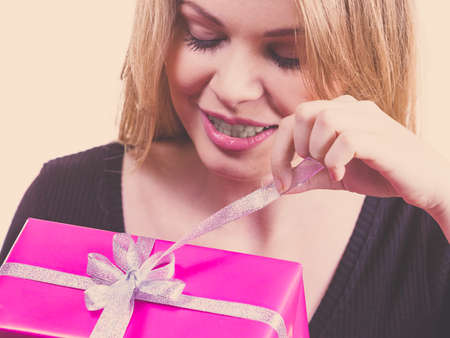 Funny cute young teenage woman being curious what is inside gift box. Female receiving present