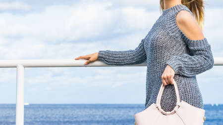 Attractive fashion woman in trendy outfit long sleeve cold open shoulder pullover outdoor on sea coast. Female model holding handbag. Stock fotó