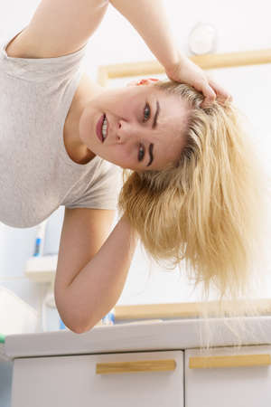 Blonde woman having problems with greasy oily hair in bathroom. Female showing scalp, scratching herself, hairdo loss, dandruff problem.