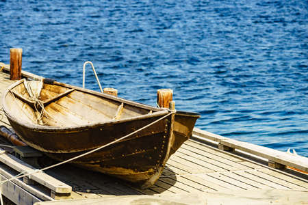 Old wooden boat on pier, fjord mountains landscape, Norway Europe