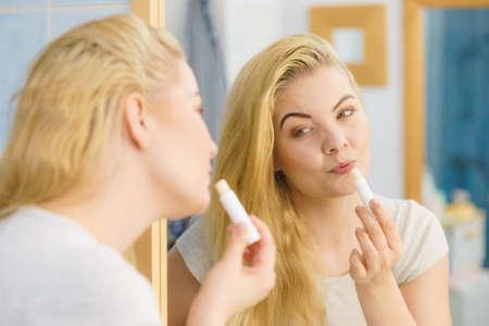 Blonde woman in bathroom putting applying lip balm moisturizing balsam, taking care of her lips skin.