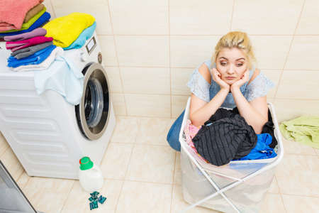 Unglückliche Frau im Badezimmer mit großem Korb mit schmutziger Kleidung. Wäschekonzept. Hausarbeit.