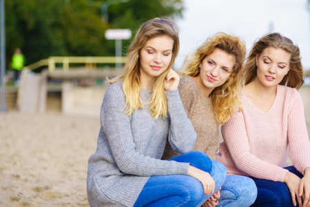 Three fashionable women wearing sweaters during warm autumnal weather spending their free time on sunny beach. Fashion models outdoor Standard-Bild - 134598650